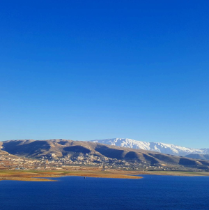 Karaoun lake with Mt. Hermon in the distance, by @georgio.copter